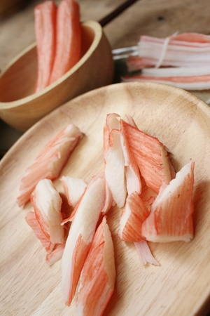tast: Crab stick in plate on brown background
