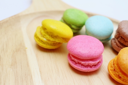 4s: Macarons in wood plate on white background.