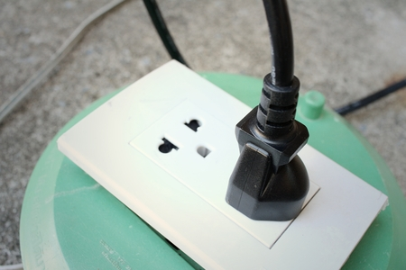 plugged: The plug is plugged into the power lines to bring electricity Stock Photo