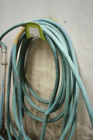 plastic conduit: Garden hose for watering plants at the park. Stock Photo