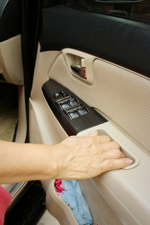 rent index: Woman is closing the car door in a car. Stock Photo