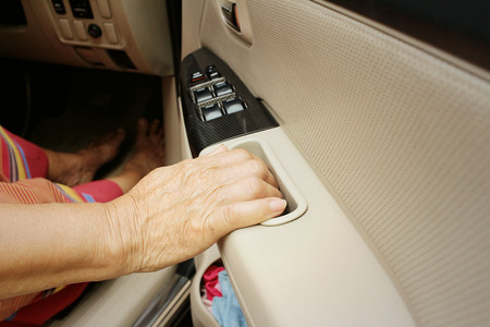 rent index: Woman is closing the car door in a car