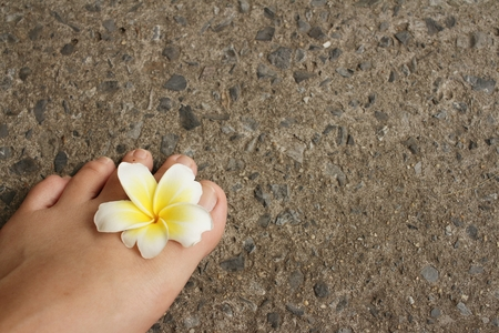 foot with plumeria flower on cement background. Stock Photo