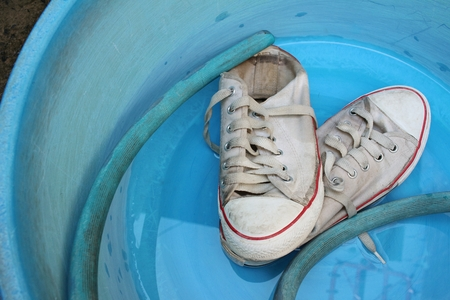 Sneakers wash enameled bowl with soapy water. Stock Photo - 60611344