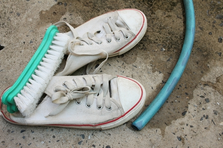 handwash: Sneakers are wash on a cement floor.