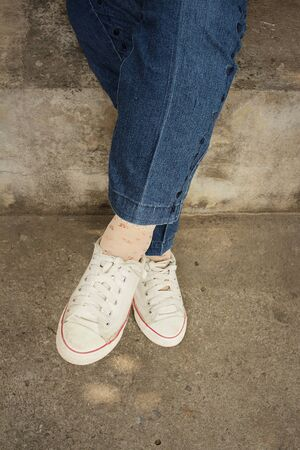 White shoes with  jeans sitting at the park Stock Photo