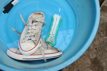 Sneakers wash enameled bowl with soapy water. Stock Photo - 60611497