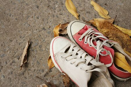 Red and white shoes on background of cement.