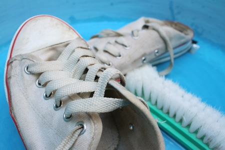 Sneakers wash enameled bowl with soapy water. Stock Photo - 60611034