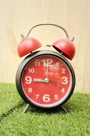 Alarm clock on background of green grass. Stock Photo
