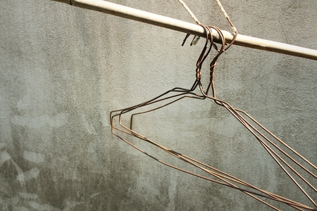 closet rod: Close up of old clothes hangers in the sunlight