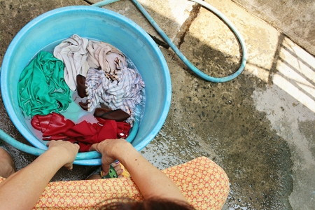 Hands washing clothes in a basin
