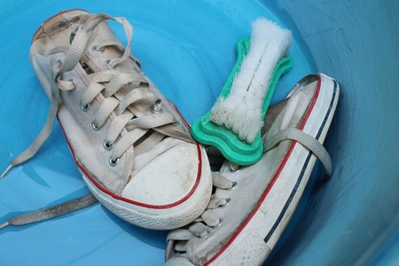 Sneakers wash enameled bowl with soapy water.