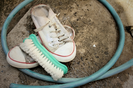 Sneakers are wash on a cement floor.