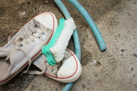 scour: Sneakers are wash on a cement floor.
