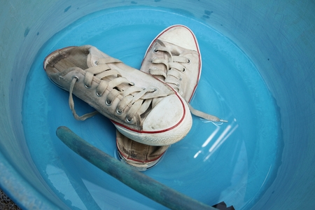 Sneakers wash enameled bowl with soapy water. Stock Photo - 60630884