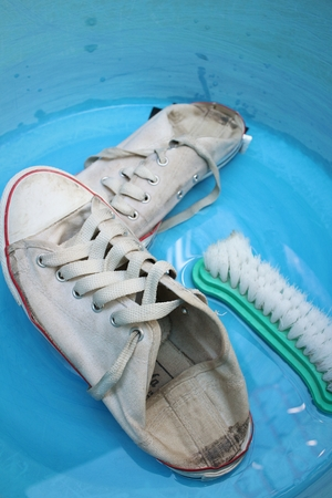 Sneakers wash enameled bowl with soapy water. Stock Photo - 60630922