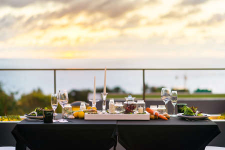 Empty glasses set in restaurant Dinner table outdoors at sunset photo