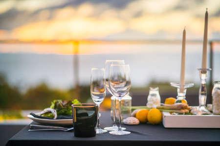 Lege glazen die in restaurant Eettafel buiten bij zonsondergang Stockfoto