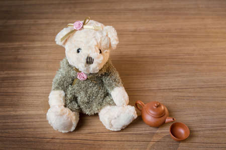 Toy teddy bear and tea kettle and cup on wooden background photo