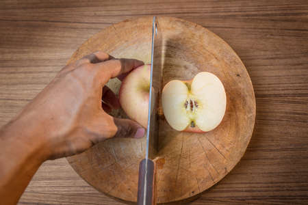Red apple and Knife on wooden cutting board photo