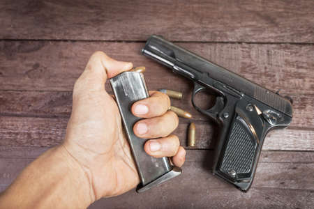 9mm: hand with bullet and Semi-automatic 9mm gun on wooden background