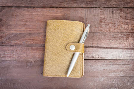 Pen on top of yellow organizer with leather cover on wooden background. photo