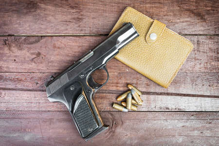 9mm: Semi-automatic 9mm gun and leather bag isolated on wooden background Stock Photo