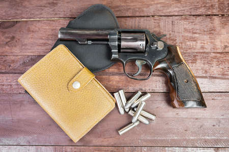 38 caliber: Black revolver gun and and leather bag over on wooden background.