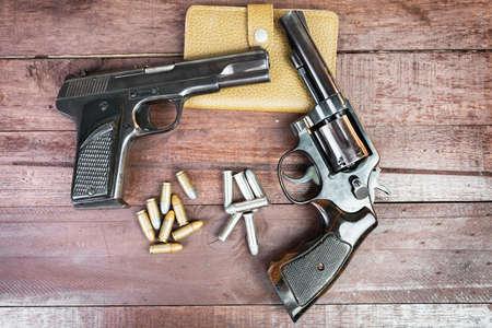 automatic pistol: Black revolver gun and Semi-automatic 9mm gun on wooden background
