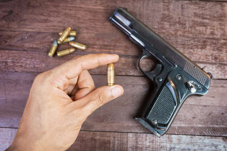 magnum: hand with bullet and Semi-automatic 9mm gun on wooden background