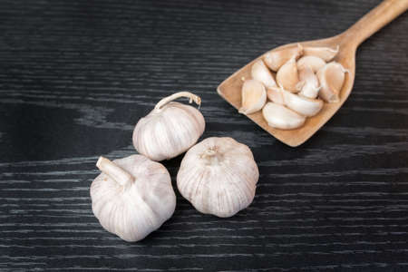 garlic clove: Garlic herb whole cloves in wooden spoons isolated Stock Photo