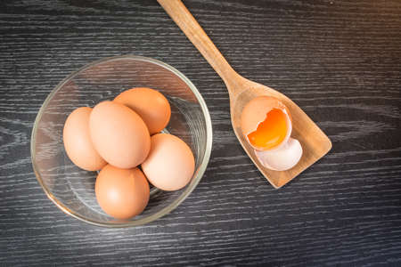 Group of brown eggs and yolk in wooden spoon on wooden background photo