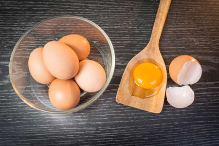 white eggs: Group of brown eggs and yolk in wooden spoon on wooden background