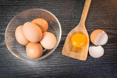 huevo blanco: Grupo de los huevos de color marr�n y yema de huevo en cuchara de madera sobre fondo de madera Foto de archivo
