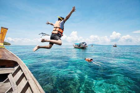 Snorkeling divers jump in the water