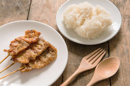 Grilled pork and sticky rice on plate, Thai food style. photo