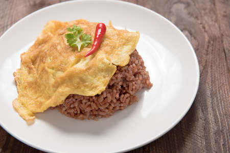 omelet: rice with omelet ,Thai omelet rice on Wood Table.