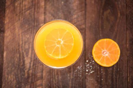 verre de jus d orange: Haut de jus d'orange dans le verre, fruits frais sur fond de bois. Banque d'images
