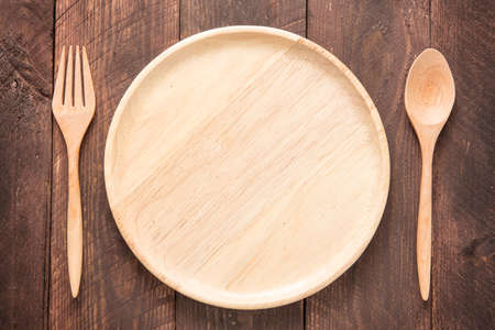 Set of fork,spoon and dish wood on wooden table. Banco de Imagens