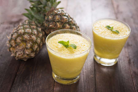 pineapple smoothie on wooden table.