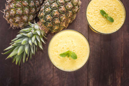 pineapple  glass: Top pineapple smoothie on wooden table. Stock Photo