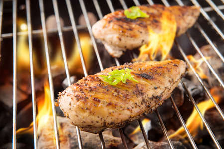 chicken breast: Marinated grilled chicken on the flaming grill.