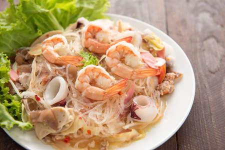 seafood salad: vermicelli salad on woooden table.