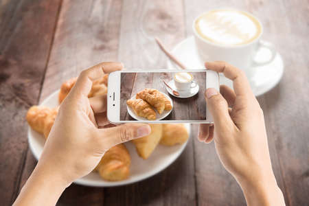 Taking photo of fresh baked croissants and coffee on wood table.