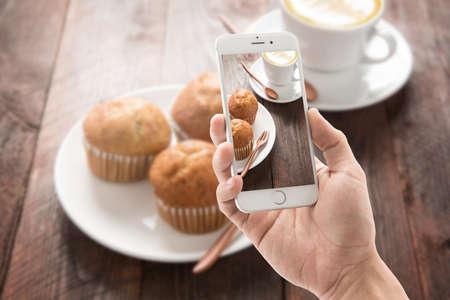Tomar la foto de magdalena y café en la mesa de madera. Foto de archivo