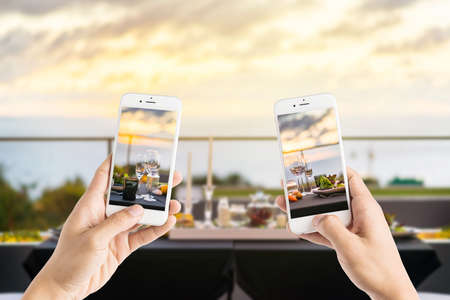 taking photo: friends using smartphones to take photos of empty glasses set in restaurant - Dinner table outdoors at sunset Stock Photo