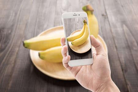 Taking photo of bananas on wooden background photo