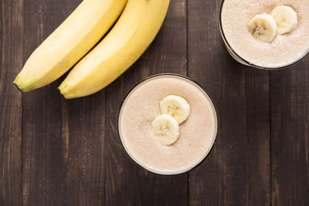 Top shot banana smoothie on wooden table photo