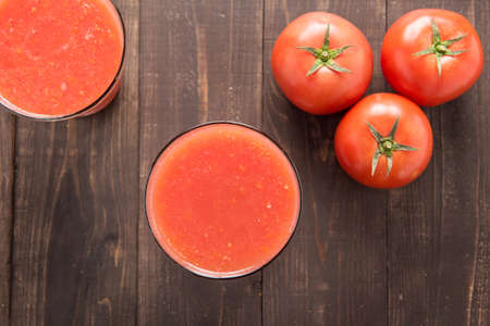 Top shot vegetable smoothie made of red ripe tomatoes on wooden table. photo